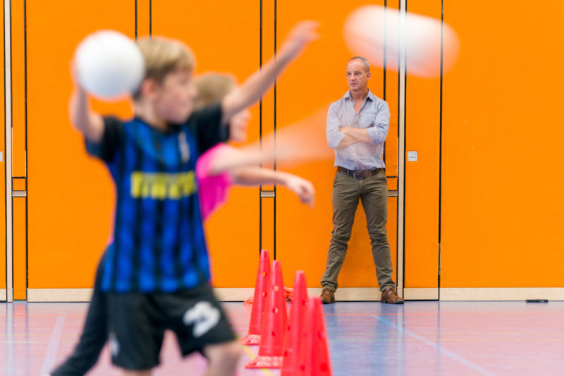 Editorial photography, subject learning and education: A sports teacher observes his students playing dodgeball.