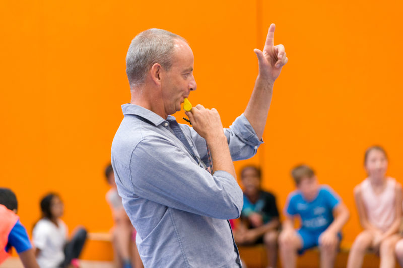Editorial photography: A teacher at work: Editorial photography, subject learning and education: A sports instructor uses his whistle in the sports hall and raises his index finger to get the attention of his class.