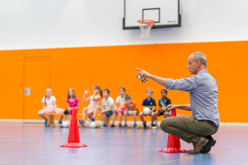 Editorial photography, subject learning and education: A sports teacher divides the teams for a ball game during lessons in a school sports hall. In his hand he has his whistle and the school keys.