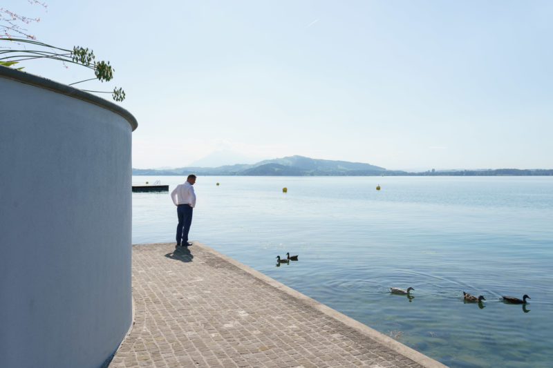 Portrait of the town: Zug at Lake Zug. A man looks at the ducks in the water on the lakeside promenade. Behind them yellow buoys on the blue Zuger See.
