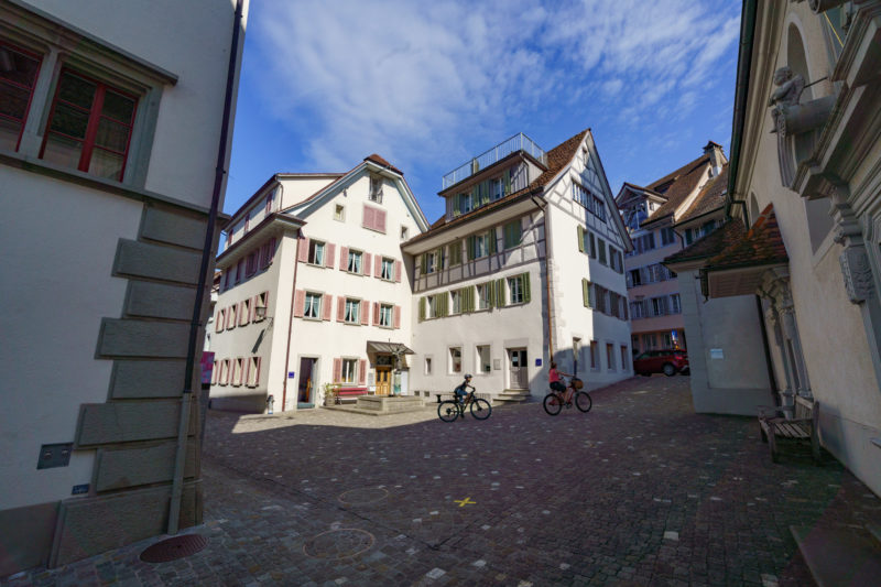 Portrait of the town: Zug at Lake Zug. Cyclists on the historic cobblestones in the winding old town of Zug.
