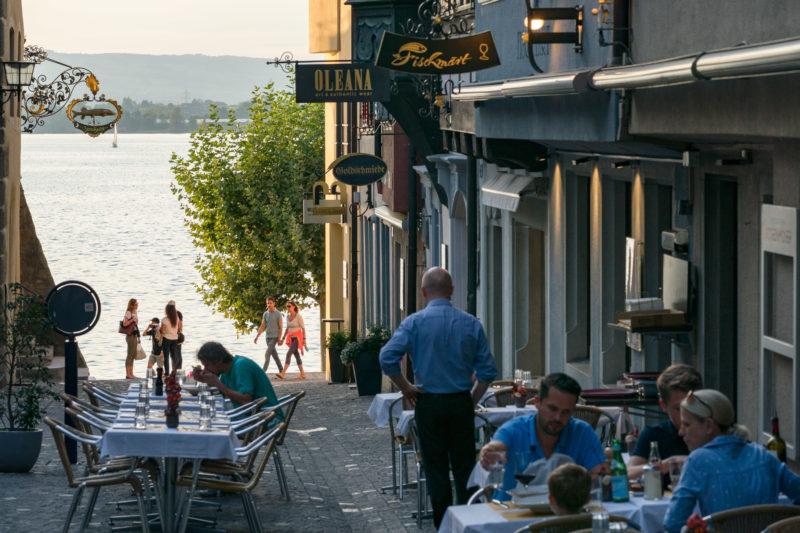 Stadtportrait: Zug am Zuger See. Menschen essen draußen vor den Restaurants, die an einer Gasse liegen, die zum See führt.