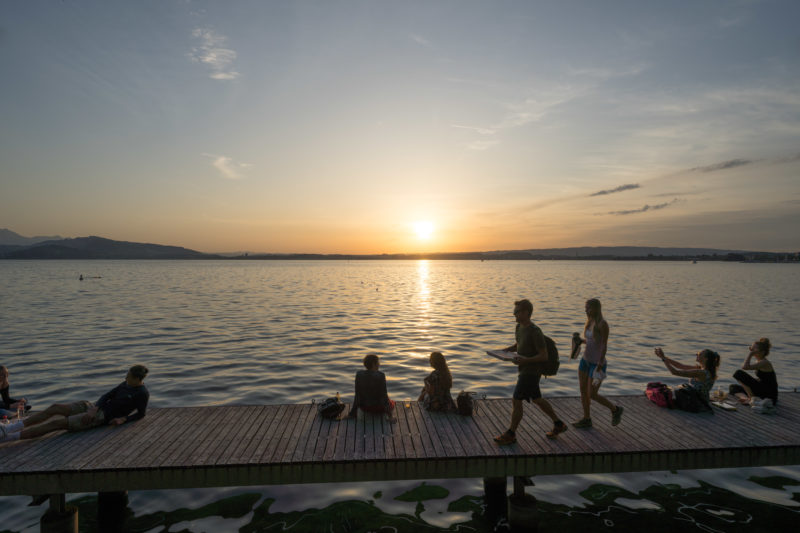 Portrait of the town: Zug at Lake Zug. Young people in the setting sun on a wooden jetty by the lake.