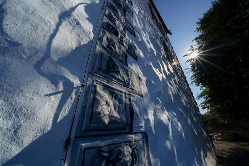 Portrait of the town: Zug at Lake Zug. Shadow play on the painted stones of an old building wall in the historic town centre. The sun shines through the branches of an old tree.