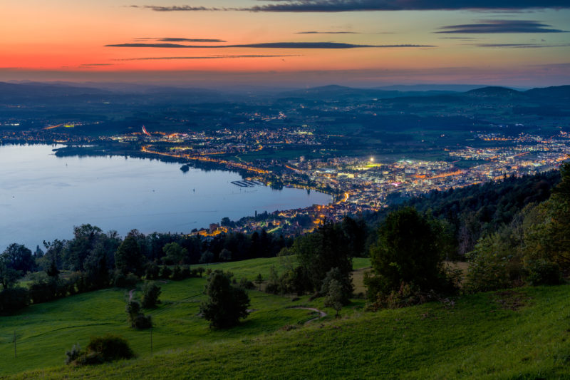 Portrait of the town: Zug at Lake Zug. Twilight shot of the illuminated city from the Zuger Berg. In front dark green meadows and trees, behind the red of the rest of the evening sky.