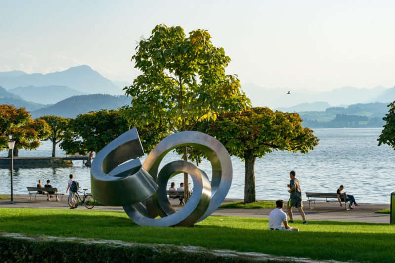 Portrait of the town: Train at Lake Zug. A sculpture made of shiny metal on the promenade on Lake Zug with strollers and people in their leisure time.