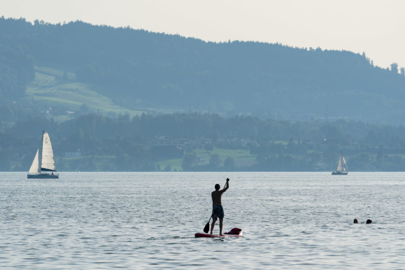 Portrait of the town: Train at Lake Zug. Sailing boats, standing paddlers and swimmers are on the move on Lake Zug.