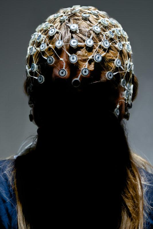 Studiofotografie: Eine Haube mit Elektroenzephalogramm-Elektroden auf dem Kopf einer Patientin. Das Blitzlicht beleuchtet nur die Haube. Das Gesicht liegt im Dunkel.