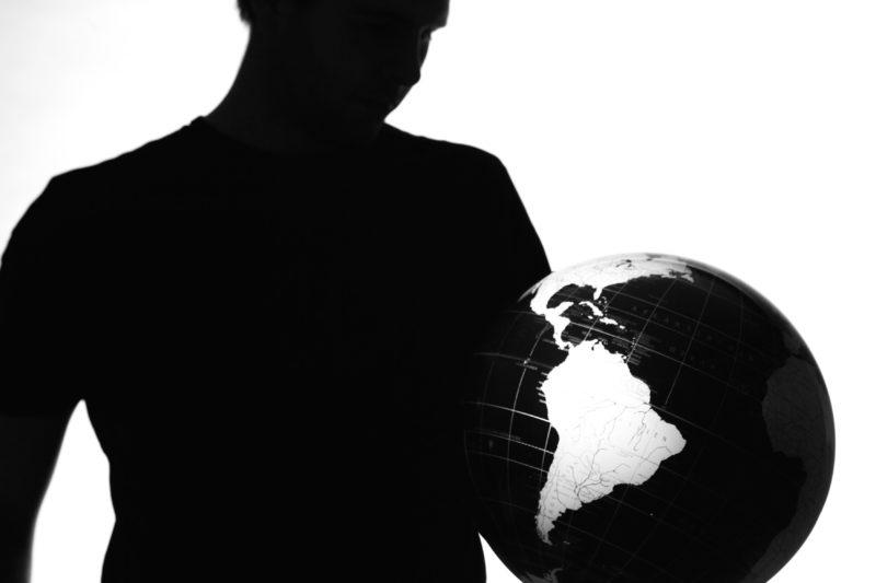 Studiofotografie: Silhouette eines Mannes der einen Globus hält.