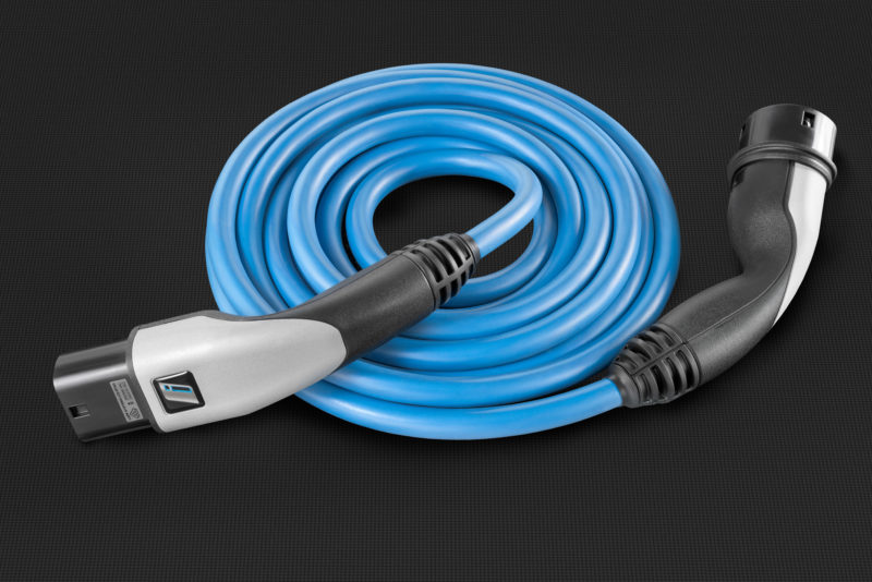 Studio photogaphy: A blue charging cable for electric vehicles. It lies rolled up on a black background. The material illustration emphasizes the surfaces of the plastics used in its manufacture.