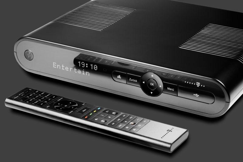 Studiofotografie: Produktfoto eines Media Receivers der Deutschen Telekom AG. Das Bild ist fast ausschließlich schwarz-weiss, aber 4 Tasten auf der Fernbedienung sind mit Farben gekennzeichnet.