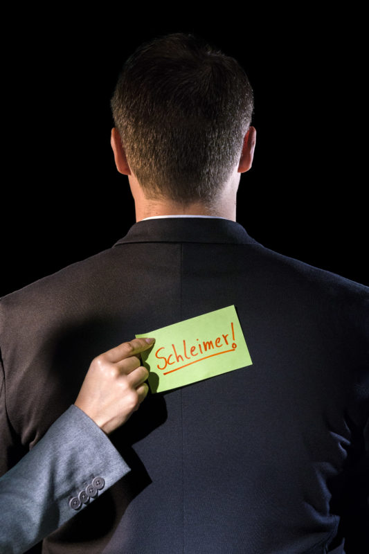 Studio photogaphy: Symbol photo on the subject of employee culture. A hand sticks a Post-It on the back of a man in a suit. It has the word suck-up written on it.