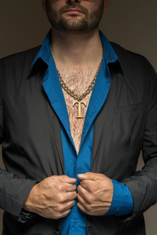 Studio photogaphy:  Symbol image for a gripping type. He has dark thick chest hair, wears an open shirt and a large amulet with a company logo around his neck.