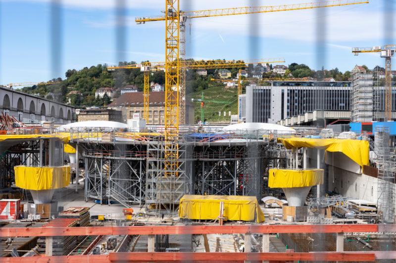 Stadtportrait Stuttgart: Blick durch die Absperrgitter auf die Baustelle des neuen unterirdischen Hauptbahnhofs des Stuttgart 21 Projektes. Dahinter das LBBW-Gebäude und die umgebenden Hügel mit dem städtischen Weinberg.