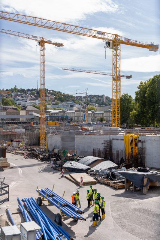 Stadtportrait Stuttgart: Blick in die noch offene Baustelle des später unter der Erde liegenden neuen Hauptbahnhofes. Kräne überragen eine Besuchergruppe mit Helmen und in Sicherheitswesten, welche sich über das Projekt Stuttgart 21 informiert.