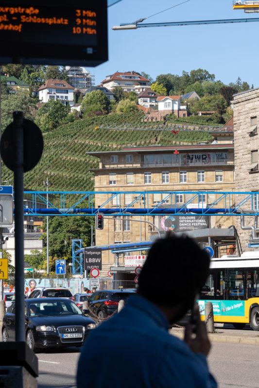 Stadtportrait Stuttgart: Vom verkehrsreichen Arnulf-Klett-Platz vor dem Stuttgarter Hauptbahnhof sieht man direkt auf die angrenzenden Weinberge des Weingutes der Stadt Stuttgart. Im Vordergrund ein Mann mit einem Smartphone an einer Bushaltestelle.