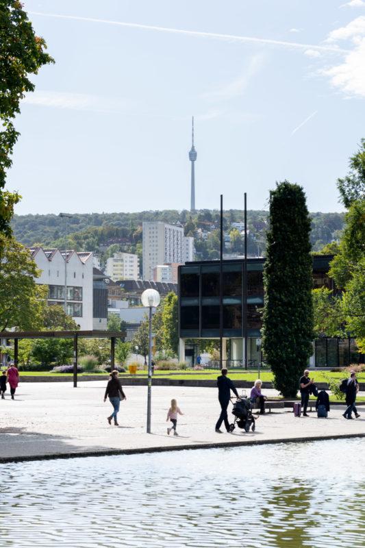 Stadtportrait Stuttgart: Blick über den Eckensee in der Stuttgarter Innenstadt auf das Landtagsgebäude und den die umgebenden Hügel überragenden Fernsehturm. Passanten sind im Gegenlicht in der Sonne unterwegs.
