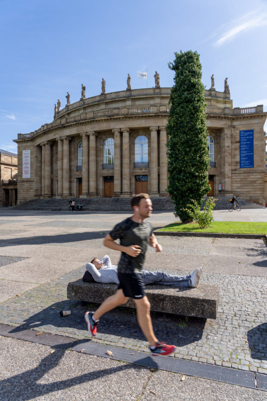 Portrait of Stuttgart: A jogger is running in front of the opera along the Eckensee. Behind him a young man lies on a stone bench and basks in the sun.