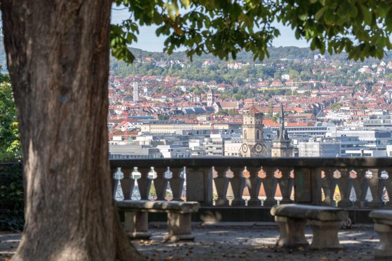 Stadtportrait Stuttgart: Blick durch die Bäume und die steinerne Balustrade um den Eugensplatz auf die darunter liegende Stadt. Gegenüber sieht man die grünen bebauten Hügel gegenüber dem Talkessel der Innenstadt.