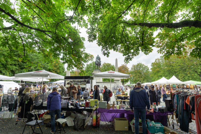 Stadtportrait Stuttgart: Under the shady chestnut trees on Karlsplatz, a large and well-attended flea market takes place every Saturday in summer. In the background you can see the always controversial equestrian statue of Wilhelm the First, King of Prussia and German Emperor.