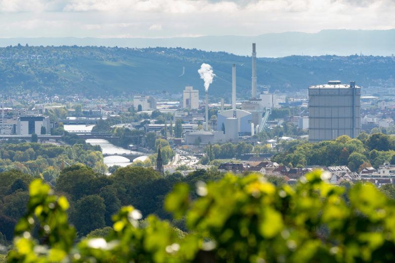 City portrait Stuttgart: View from the vineyards below the Burgholzhof in direction Neckar with Wangen, Untertürkheim and the east of Stuttgart. The gas boiler and the power plant dominate the cityscape. The green hills with the vineyards surround the view.