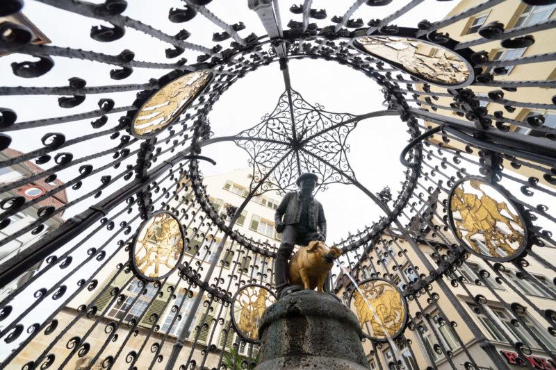 Stadtportrait Stuttgart: Der Hans-im-Glück-Brunnen ist ein nach der gleichnamigen Märchenfigur benannter Brunnen in Stuttgart-Mitte und steht auf einem kleinen bei nächtlichen Club und Barbesuchern sehr beliebten Platz an der Geißstraße.