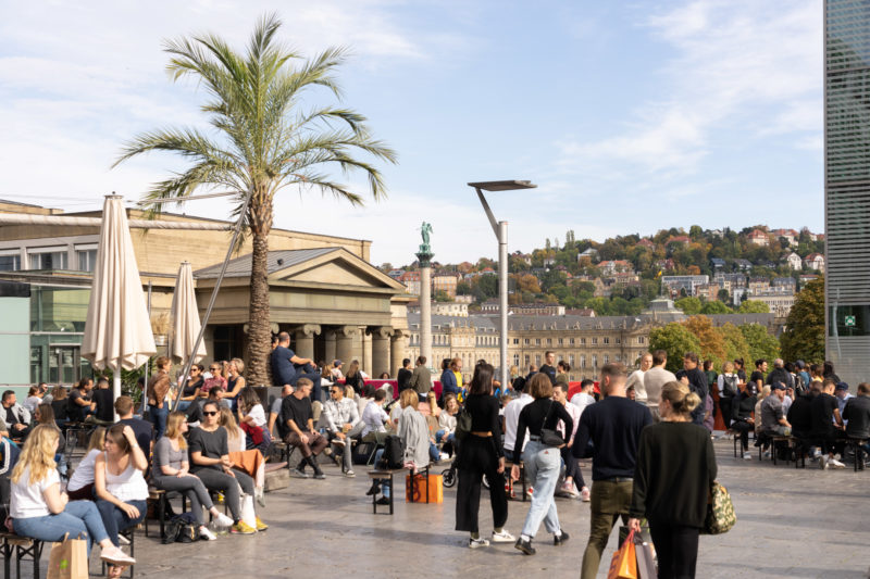 Stadtportrait Stuttgart: On the Kleiner Schlossplatz, guests of a café sit in the sun. In the background you can see the New Castle and the surrounding built-up slopes.