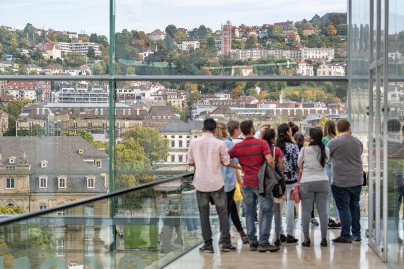 Stadtportrait Stuttgart: Eine Gruppe von Touristen besucht den obersten Stock des Kunstmueums Stuttgart und genießen den Blick auf die umliegenden bebauten Hänge.