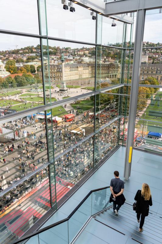 Stadtportrait Stuttgart: Im obersten Stock des Kunstmuseums am Stuttgarter Schlossplatz hat man einen schönen Blick auf die vielen Passanten auf dem Schlossplatz und die umgebenden Hänge mit den vielen Stadthäusern.