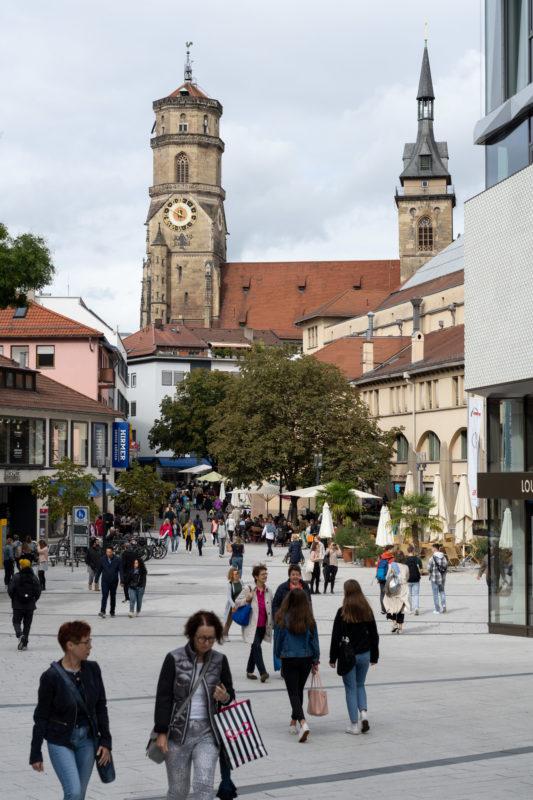 Stadtportrait Stuttgart: Der Platz vor der Markthalle in der Innenstadt ist seit dem Bau des angrenzenden Dorotheenquartiers von Einkaufenden belebt. Im Hintergrund ist man die Türme der Stiftskirche.