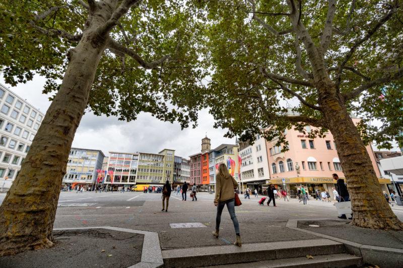 Stadtportrait Stuttgart: Der Stuttgarter Marktplatz ist bis auf wenige Platanen um den Brunnen außerhalb der Marktzeiten eine leere Fläche, die von den vielen Passanten meist mit schnellen Schritten überquert wird.
