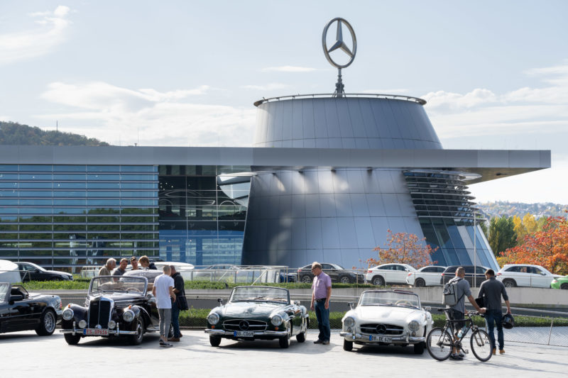 Stadtportrait Stuttgart: Auf dem Vorplatz des Mercedes-Benz-Museums stehen eine Reihe historische Mercedes Cabrios. Die Szene wird von einem großen Mercedes Stern auf dem Dach der angrenzenden Mercedes Niederlassung überragt.