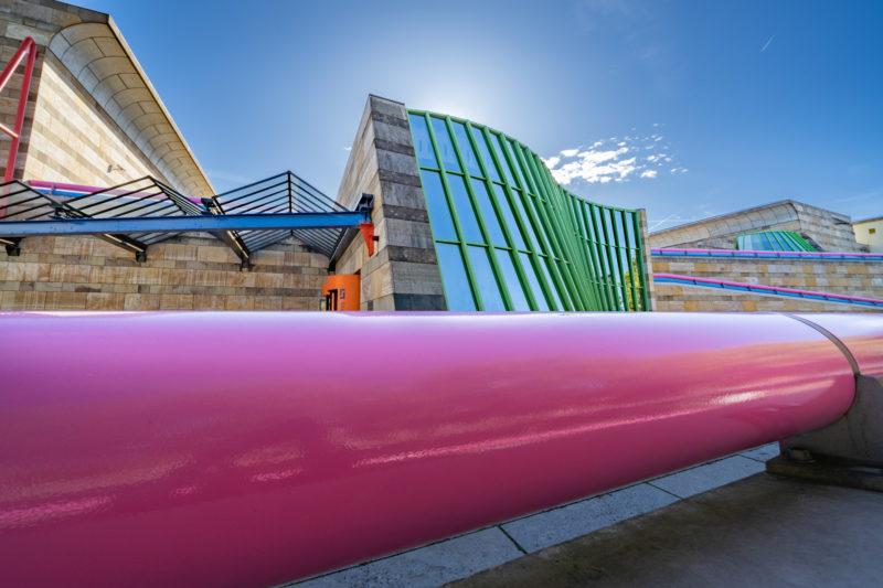 Stadtportrait Stuttgart: Die berühmte von James Stirling entworfene postmoderne Architektur der Eingangsfront der Neuen Staatsgalerie Stuttgart mit ihrer geschwungenen grün eingefassten Glasfront und der Metallbrüstung in rosa. Dahinter der blaue Himmel und die dazugehörigen Gebäudeteile aus Travertin und Sandstein.