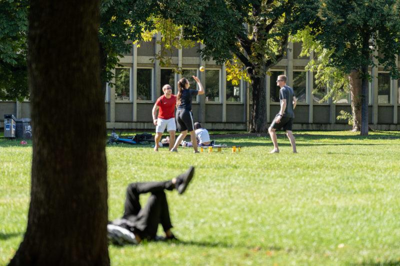 Stadtportrait Stuttgart: Im Park bei der Universität spielen junge Leute mit dem Ball während andere entspannt in der Sonne auf der Wiese liegen.