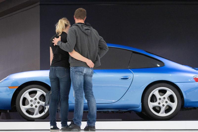Stadtportrait Stuttgart: Im Porsche-Museum sieht man auch die modernsten Versionen der Porsche Sportwagen. Ein Paar steht umschlungen vor einem blauen Modell 911.