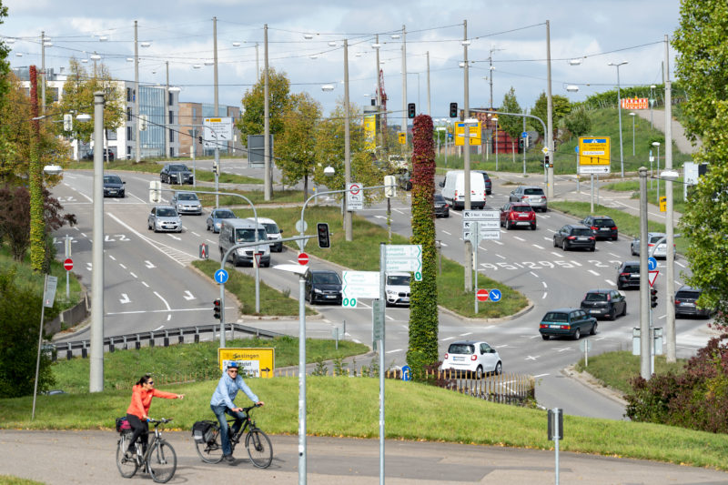 Stadtportrait Stuttgart: Blick auf die große Kreuzung am Pragsattel, die die City mit dem Stuttgarter Stadtteilen Feuerbach und Zuffenhausen im Nordosten verbindet. Im Hintergrund Weinberge, im Vordergrund Radfahrer.