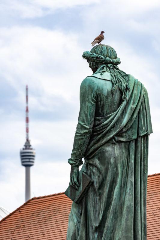 Stadtportrait Stuttgart: Eine Taube sitzt auf der 1839 aufgestellten Bronzeplastik von Friedrich Schiller auf dem Schillerplatz. Dieses Denkmal war eines der ersten großen Dichterdenkmäler in Deutschland. Im Hintergrund sieht man den Stuttgarter Fernsehturm.