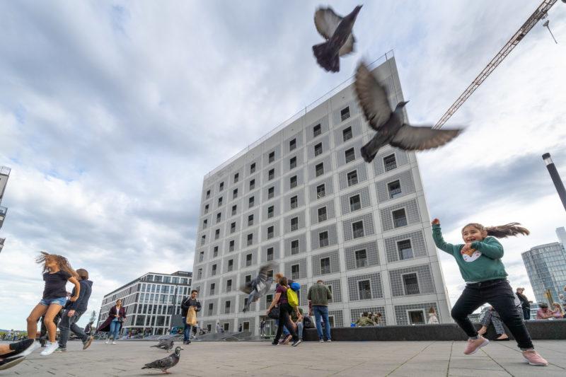 Stadtportrait Stuttgart: Am Pariser Platz fliegen Tauben auf, nachdem ein kleines Mädchen mit ihnen spielen will. Im Hintergrund das moderne Gebäude der Stadtbibliothek.