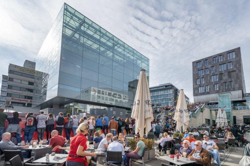Stadtportrait Stuttgart: Bei einer Veranstaltung auf dem Schlossplatz sitzen die Gäste eines Cafes direkt neben den Zuschauern. Im Hintergrund die Fassade des gläsernen Kunstmuseums Stuttgart links und der Treppen daneben.
