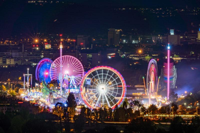 Stadtportrait Stuttgart: Eine Nachtaufnahme der beleuchteten Fahrgeschäfte beim Volksfest auf dem Cannstatter Wasen. Vor allem die Riesenräder zeichnen schöne Spuren in bunten Farben.