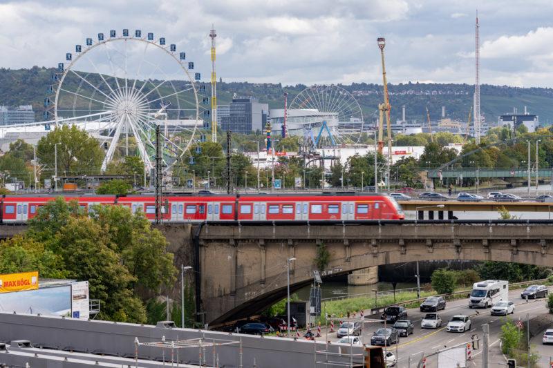 Stadtportrait Stuttgart: Die Brücken über den Neckar mit dem Wasen im Hintergrund, auf dem gerade das Cannstatter Volksfest aufgebaut wird. Eine S-Bahn fährt im Vordergrund gerade Richtung Hauptbahnhof, während darunter und daneben der Autoverkehr rollt.