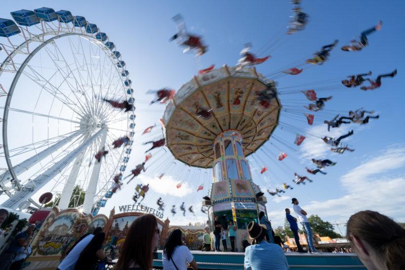 Stadtportrait Stuttgart: Riesenrad und Kettenkarussell beim Volksfest auf dem Cannstatter Wasen. Durch die längere Verschlusszeit scheinen die Besucher durch die Luft zu wirbeln.