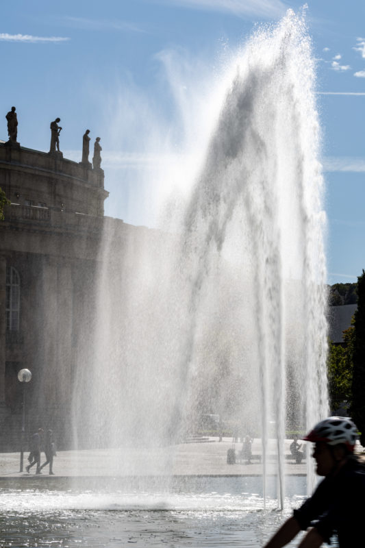 Stadtportrait Stuttgart: Die große Wasserfontäne des Eckensees im Gegenlicht bildet zusammen mit einem Radfahrer, den Passanten und den Skulpturen auf dem Dach der Stuttgarter Oper ein harmonisches Bild.
