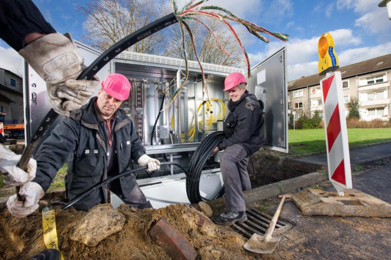 Industriefotografie: Techniker der Deutschen Telekom AG verlegen Daten- und Telefonkabel.