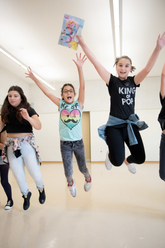 Editorial photography, subject learning and education: Girls jump into the air screaming and cheering during lessons in a theatre pedagogy workshop.