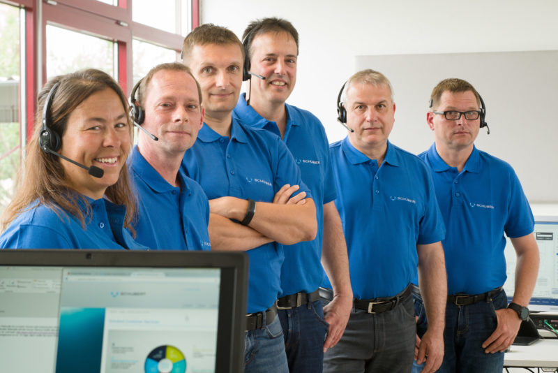 Group photo: Six employees of a company stand one behind the other in a row. All wear the blue T-shirt with the company name. The photo is taken with a light telephoto lens with tilt mechanism so that the oblique focus is on all faces.