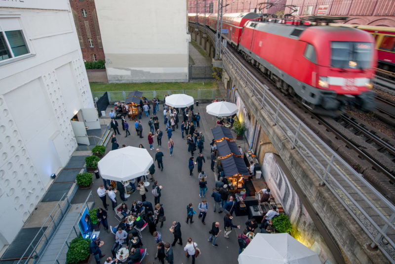 Editorial photography as event photography and fair photography: At a company event at the Alexanderplatz transformer station in Berlin, trains thunder along the adjoining elevated track system. Downstairs the participants in the courtyard of the event location take food at small tents.