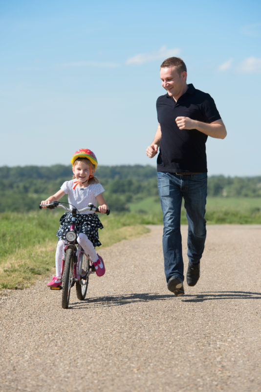 Industrial photography: Editorial photography, subject learning and education: Editorial photography: A father teaches his young daughter in the sun on a dirt road cycling.