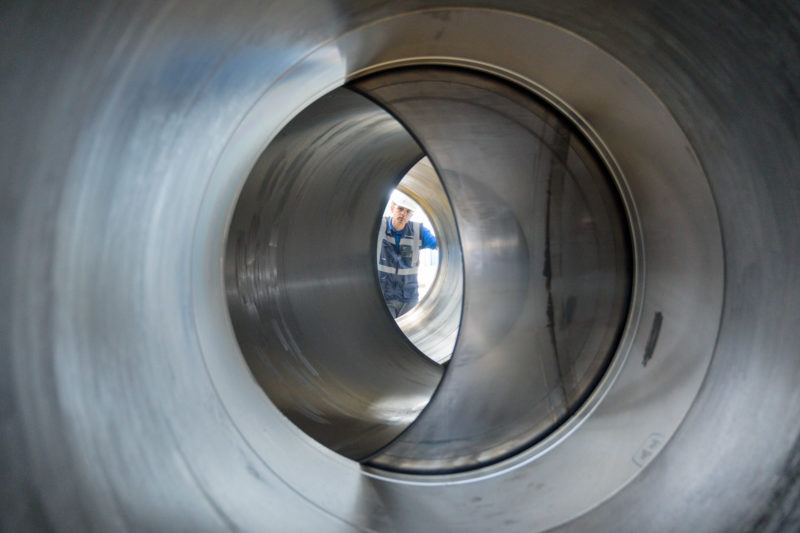 Industrial photography: An employee looks through the huge valve that will later be installed in a gas pipeline. The spherical closure element regulates the flow by rotating it in the valve.