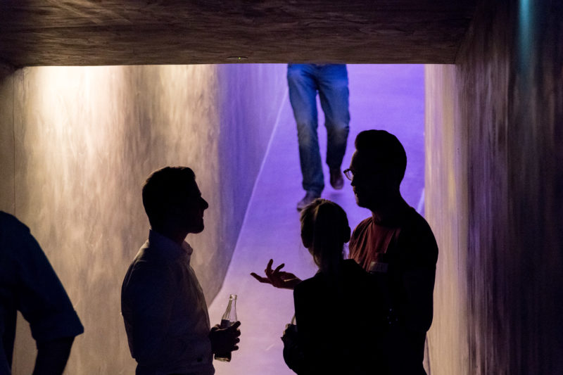 Event photography, editorial photography:  In the break of a company event, several participants discuss what they have experienced. While one sees their silhouettes, someone walks in the background along the colourfully illuminated corridor.